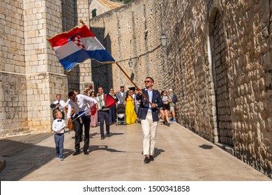 DUBROVNIK, CROATIA- AUGUST, 2019: A man waving the Croatian flag at the head of a procession through the old town stone streets of Dubrovnik.