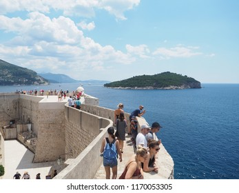 Dubrovnik, Croatia - July 05, 2018: Walking on Dubrovnik old town city walls with a view on the bay with Lokrum island in front of the city. People are relaxing and enjoying the amazing view