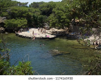 Dubrovnik, Croatia - July 06, 2018: The Dead Sea, a natural small salty lake in the center of Lokrum Island, Dubrovnik, Croatia. People are relaxing in a sunny summer day