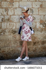 DUBROVNIK, CROATIA- July 1, 2019: A japanese girl tourist standing against a wall and browsing the internet in old town Dubrovnik.