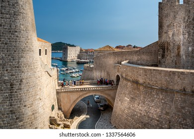 DUBROVNIK, CROATIA - JULY 18, 2015: Daytime view of ancient fortress stone walls with incidental people and harbor in the background in Dubrovnik Croatia July 18, 2015