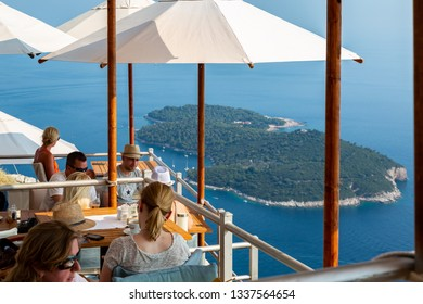 DUBROVNIK, CROATIA - JULY 18, 2015: Daytime top view of people at a restaurant on a mountain top with an island in the Adriatic sea in the background. Dubrovnik Croatia July 18, 2015.