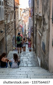 DUBROVNIK, CROATIA - JULY 18, 2015: Perspective daytime view of people on a narrow street with steep stairs in the old town of Dubrovnik Croatia July 18, 2015.