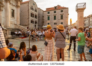 DUBROVNIK, CROATIA - JULY 18, 2015: City view of people in the old town at the town square looking at musicians holding a free outdoor concert in Dubrovnik Croatia July 18, 2015.