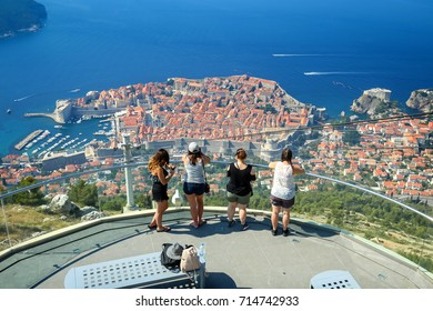 DUBROVNIK, CROATIA - JULY 19, 2017 : Tourists at a viewpoint on Srd hill looking at Dubrovnik panorama in Dubrovnik, Croatia.