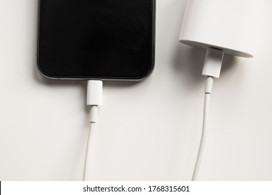 Dubrovnik, Croatia - July 2, 2020: Apple iPhone charging with charger adapter isolated on white background