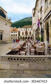 DUBROVNIK, CROATIA - JUNE 28, 2015: Cafe scene of Pred Dvorom Street, with locals and tourists, in Dubrovnik, Croatia