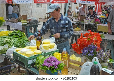 DUBROVNIK, CROATIA - MAY 22, 2010: A man offers cheeses and other products of the country, in the open-air market of the city