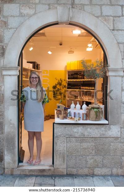 DUBROVNIK, CROATIA - MAY 26, 2014: Saleswoman in store front on Stradun in Dubrovnik, Croatia