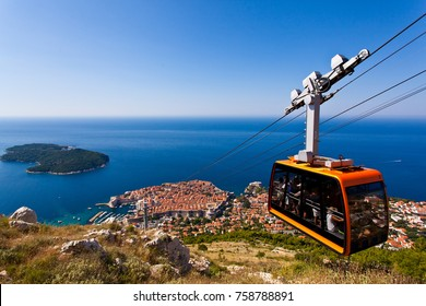 Dubrovnik, Croatia - November 20, 2017: Cable Car takes tourists from the old town to the top of Mount Srd. Old town city wall and the Adriatic sea in background.