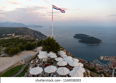 Dubrovnik Croatia restaurant bar outdoor dining. View from Mountain Srd to Dubrovnik Old Town and Lokrum Island. Croatian Flag at sunset.