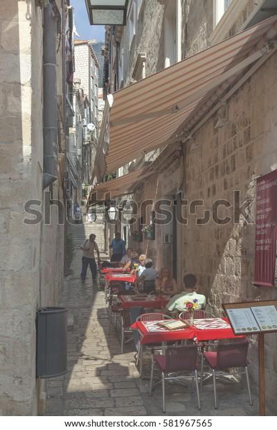 DUBROVNIK, CROATIA - SEPTEMBER 30, 2009: Narrow street with restaurant in  Dubrovnik