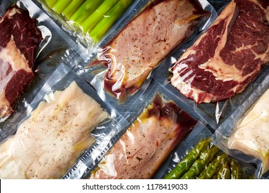 Duck breast, chicken breast, beef steak and asparagus vacuum sealed ready for sous vide cooking, on black background, top view