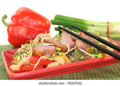 Duck breast with fried noodles, fresh vegetables and radish sprouts