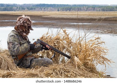 duck hunter charges his shotgun next to the hunting blind of reeds on the lake