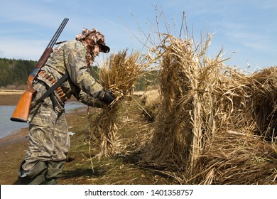 duck hunter with a shotgun making a hunting blind of reeds on the lake