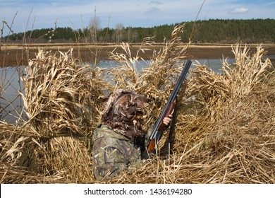 duck hunter with a shotgun sitting in the shelter during waterfowl hunting