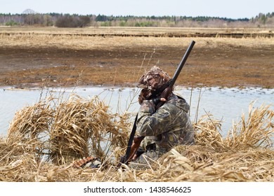 duck hunter with a shotgun sitting thinking during waterfowl hunting