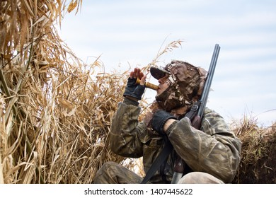the duck hunter sits in the blind of the reeds and lures the ducks
