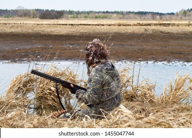 duck hunting in camouflage with a shotgun sitting next to the lake during waterfowl hunting