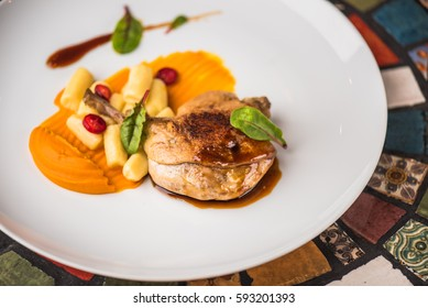 Duck leg with garnish in a white plate on a multicolor table close-up. Healthy food.