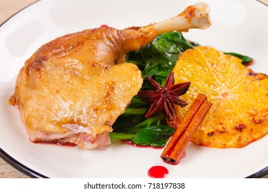 Duck leg with spinach, orange and spices: cinnamon and star anise in red wine sauce, horizontal