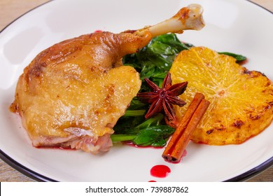 Duck leg with spinach and orange in sweet and sour berry sauce, white plate on rustic wooden table