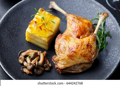 Duck legs confit with potato gratin and mushroom sauce. Restaurant serving. Close up.