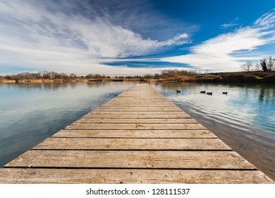 A duck pond view from a wood pontoon with some ducks in the distance. Reflections of the vibrant blue sky on the water surface.