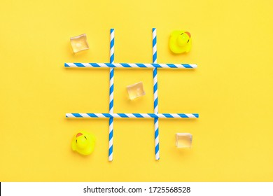 duck toy, ice cubes, paper tubes with blue stripes for drinks on a yellow background. Sea battle, tic tac toe game concept Creative composition Flat lay Top view
