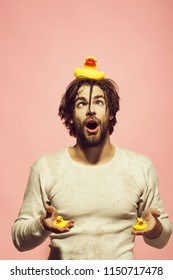 duckling toy at surprised man in bath or shower with wet hair on pink background, hygiene and skincare, health and wakeup