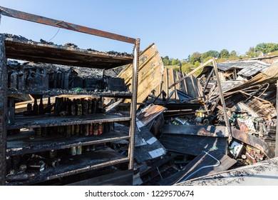 DUCLAIR, FRANCE - OCTOBER Circa, 2018 : Damaged CARREFOUR MARKET supermarket after arson fire with burn debris of can beer brand LEFFE on burnt shelves