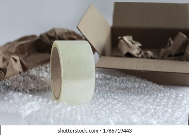 Duct tape on the background of corrugated boxes, packaging paper and bubble wrap. Tools for packaging products on a white background. Packer. Focus on the tape.