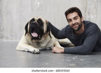 Dude and dog lying in studio, portrait