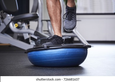Dude jogging on bosu ball in gym, close up