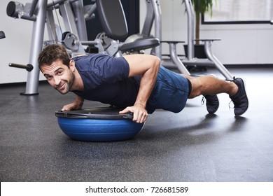 Dude performing press ups on bosu ball, portrait