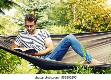 Dude reading on hammock in garden
