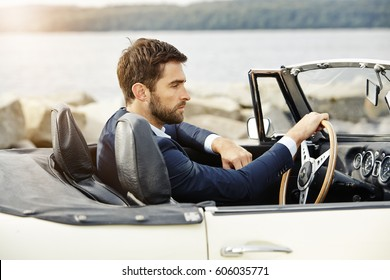 Dude in sports car wearing suit