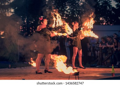 "Dudutki / Belarus - june 22, 2019: 4th international festival ""Svyata Sontsa - 2019"", fire-show competition. young women dance with burning fans against the background of the public"