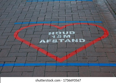 """Due to Coronavirus disease (COVID-19) scourge, Red heart tape on footpath with word in dutch """"HOUD 1,5 M AFSTAND"""" """"KEEP 1.5 M AWAY"""" Reminding people to keep social or physical distancing, Amsterdam."""