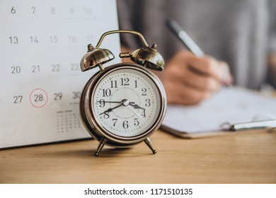 due date calendar with alarm clock on office desk and blur business woman working in background