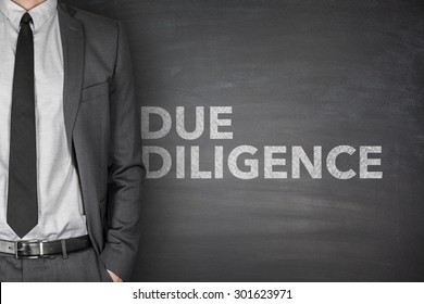 Due diligence on black blackboard with businessman