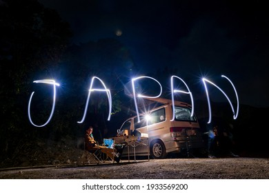 Due to long exposure photography noise and motion blur on the subject is unavoidable of a camper van with light painting of Japan wording in cold night.
