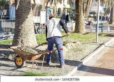 Aufgrund der Sturmflucht zieht der Arbeitnehmer Sand aus den Blumenbeeten ab