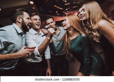 Duet. Trendy Nightclub. Have Fun. Ledy in Green. Dress. Background. Cheerful. Smile. Smiling Girl.Singing Songs. Handsome Men. Beautiful Girls. Friends at Karaoke Club. Karaoke Club. Celebration.