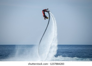 Dugi Rat, Croatia - October 20, 2018: A man is doing acrobatics with flyboard attached to jet ski close to the shore in Dugi Rat, Croatia.