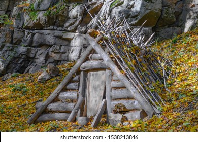 Dugout (or dug-out, pit-house, earth lodge, cellar dug) from logs in autumn forest. Traditional shelter for humans and livestock based on hole  into ground. Natural historical museum of dugouts. Toned