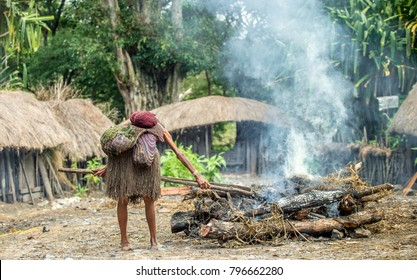 Dugum Dani tribe village. Woman of Dugum Dani tribe cooks food, uses an earthoven method of cooking pig.  West Papua. New guinea Island.
