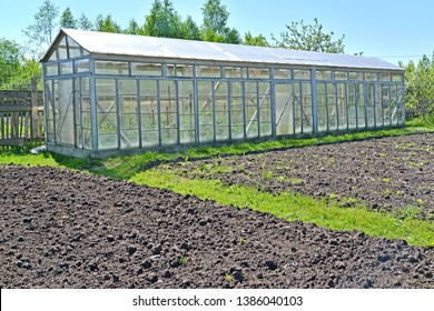 The dug-up beds and the greenhouse from glass frames on the seasonal dacha