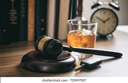 DUI concept. Law gavel, alcohol and car keys on a wooden desk, dark background